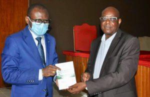 L'écrivain Pascal Bamouni remettant son livre au ministre de la justice Réné Bagoro à gauche